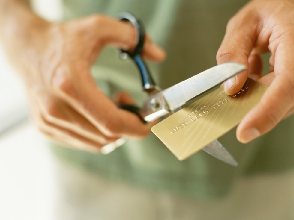 close-up of human hands cutting a credit card by scissors --- Image by © Royalty-Free/Corbis